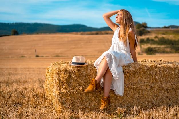 Estilo de vida, jovem camponesa loira cabelos lisos com vestido branco, aproveitando o sol