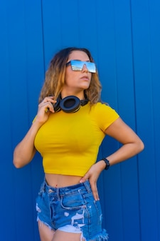 Estilo de vida, loira caucasiana com camiseta amarela. mulher jovem posando com olhar sensual com fones de ouvido musicais e óculos de sol