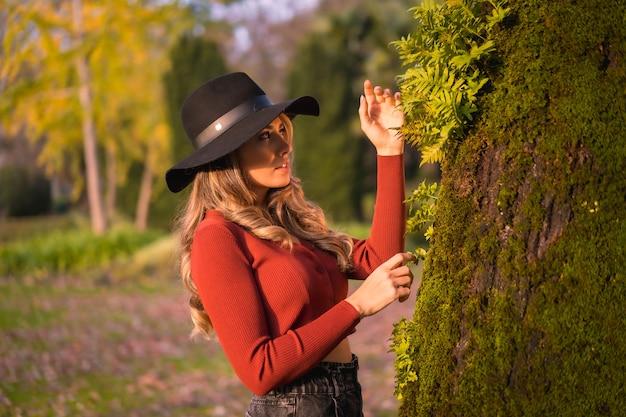 Estilo de vida loira caucasiana com um suéter vermelho e chapéu preto curtindo a natureza em um parque com árvores retrato da jovem olhando para a bela árvore com musgo no outono