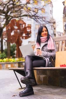 Estilo de vida, menina morena caucasiana trabalhando com laptop em um parque, sentada em um banco