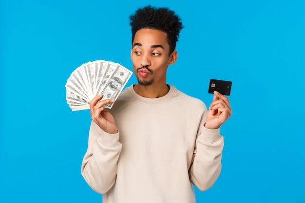 Estilo de vida moderno, negócios e conceito de finanças. alegre cara afro-americana feliz pensando como desperdiçar dinheiro, beijando dólares em dinheiro e segurando o cartão de crédito, ganhar o prêmio, parede azul de pé