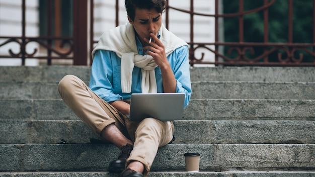 Estilo de vida moderno. trabalho remoto online. homem de negócios sentado na rua com laptop trabalhando fumando.