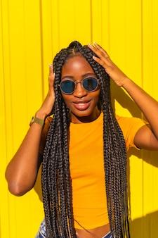 Estilo de vida, muito negra com longas tranças, camisetas amarelas e jeans curtos em uma parede amarela. sorrindo com óculos de sol