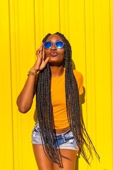 Estilo de vida, muito negra com longas tranças, camisetas amarelas e jeans curtos em uma parede amarela.