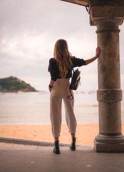 Estilo de vida na cidade com uma menina loira de calça branca e uma jaqueta de couro perto da praia. fotos ao lado de uma coluna com vista para o mar por trás