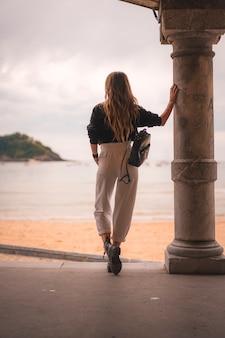 Estilo de vida na cidade com uma menina loira de calça branca e uma jaqueta de couro perto da praia. fotos ao lado de uma coluna na praia