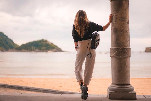 Estilo de vida na cidade com uma menina loira de calça branca e uma jaqueta de couro perto da praia. fotos ao lado de uma coluna olhando a bela praia