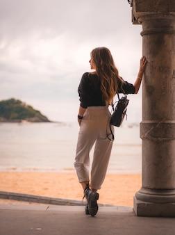 Estilo de vida na cidade com uma menina loira de calça branca e uma jaqueta de couro perto da praia. fotos ao lado de uma coluna olhando para o mar e para a esquerda