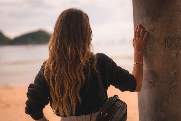 Estilo de vida na cidade com uma menina loira de calça branca e uma jaqueta de couro perto da praia. muito feliz em algumas águas rasas na praia por do sol