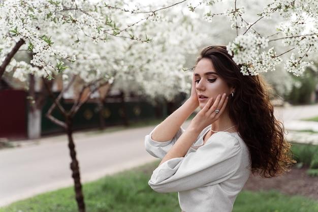 Estilo de vida na primavera. posando de modelo perto de árvores florescendo brancas sem máscara de campo ao ar livre. menina sonhadora com cabelo encaracolado.