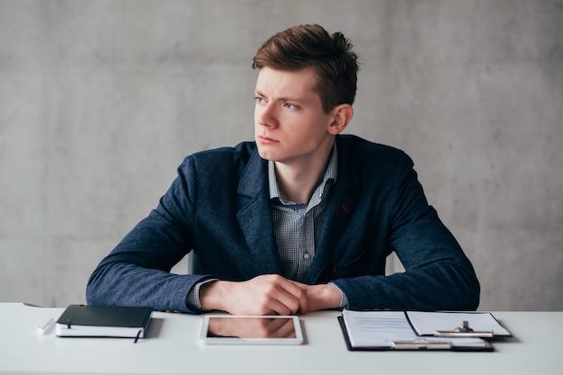 Estilo de vida no escritório. retrato de homem de negócios jovem sentado na mesa sobre o fundo da parede cinza. expressão facial confiante.