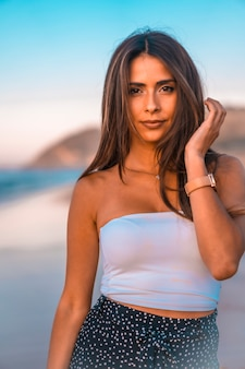 Estilo de vida, olhar de uma jovem morena sorridente em um top branco e uma minissaia na praia