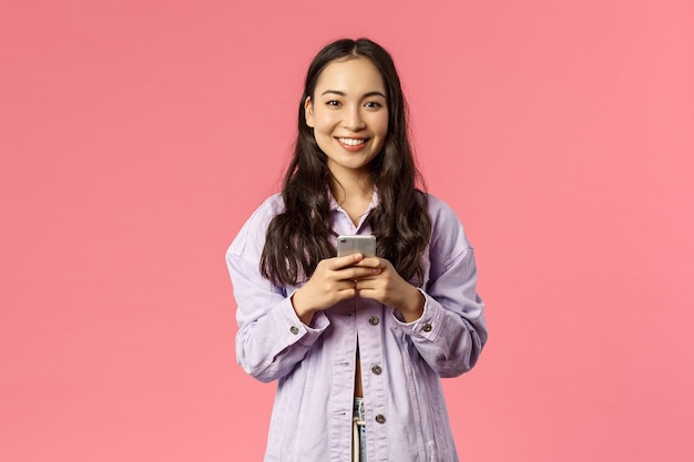Estilo de vida online, pessoas e conceito de beleza. jovem alegre e elegante usando telefone celular e sorrindo satisfeita com a câmera, conversando durante o bloqueio, usando aplicativo educacional, fundo rosa