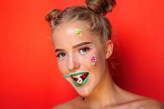 Estilo de vida, pessoas, beleza, conceito criativo - bela jovem segura nas mãos doces sorrindo amplamente. menina elegante com maquiagem brilhante e doces nas mãos, isolada no fundo rosa