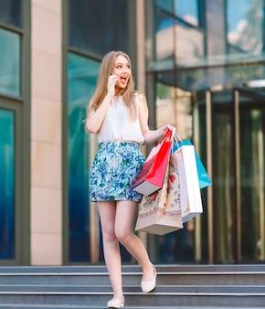 Estilo de vida retrato jovem loira, com sacos de compras, saindo da loja e falando pelo telefone móvel.