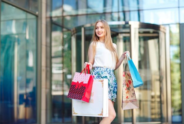 Estilo de vida retrato jovem loira, com sacos de compras, saindo da loja.