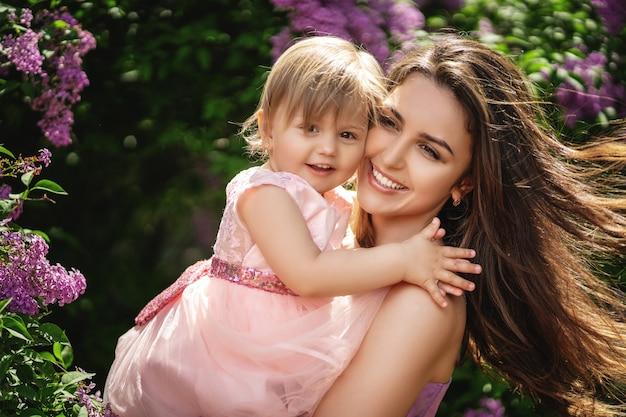 Estilo de vida retrato mãe e filha em felicidade do lado de fora nas árvores florescendo