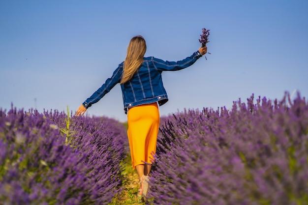 Estilo de vida rural, jovem loira caucasiana em jaqueta jeans e vestido laranja