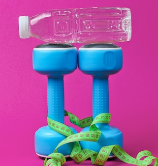 Estilo de vida saudável ainda vida. halteres, régua, garrafa de água em rosa.