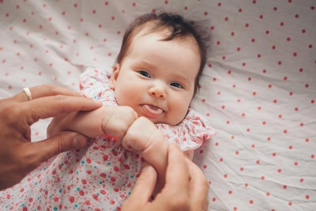 Estilo de vida saudável, bebê recém-nascido de fertilização in vitro fechou os punhos na frente dele e mostra a língua