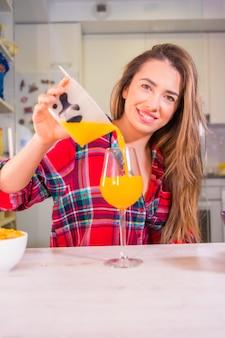 Estilo de vida saudável, bela loira caucasiana com uma camisa xadrez vermelha servindo-se de um suco de laranja fresco no café da manhã