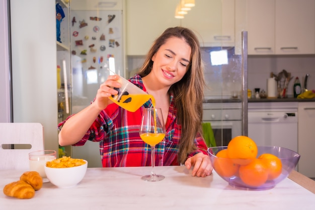 Estilo de vida saudável, bela loira caucasiana com uma camisa xadrez vermelha servindo-se de um suco de laranja fresco