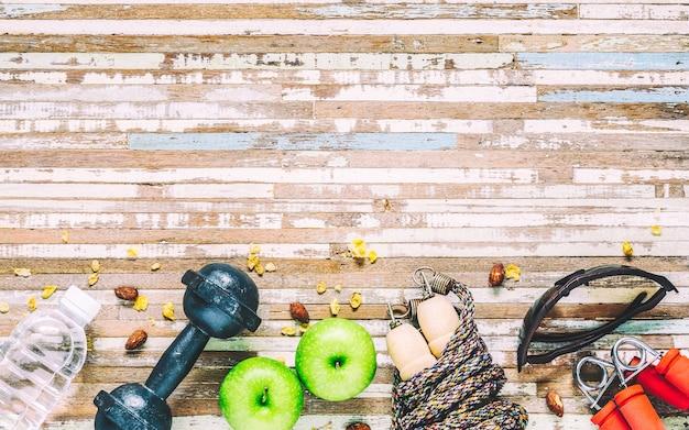 Estilo de vida saudável, comida saudável e equipamentos de esporte em fundo de madeira