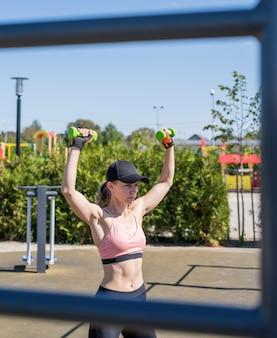 Estilo de vida saudável e ativo. esportes e condicionamento físico. mulher feliz em roupas esportivas, malhando com halteres no campo de esportes em um dia ensolarado de verão, treinando os ombros