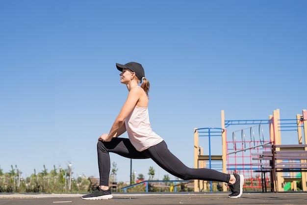 Estilo de vida saudável e ativo. esportes e condicionamento físico. mulher feliz em roupas esportivas, malhando na quadra de esportes em um dia ensolarado de verão, aquecendo