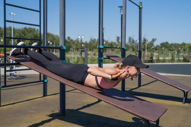Estilo de vida saudável e ativo. esportes e condicionamento físico. mulher feliz em roupas esportivas, malhando no campo de esportes em um dia ensolarado de verão, treinando-a de volta
