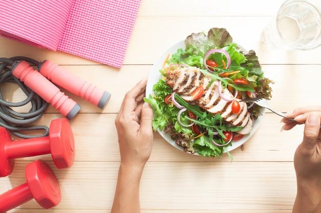Estilo de vida saudável e conceito de dieta, mesa de madeira vista superior com prato de salada e equipamentos de fitness
