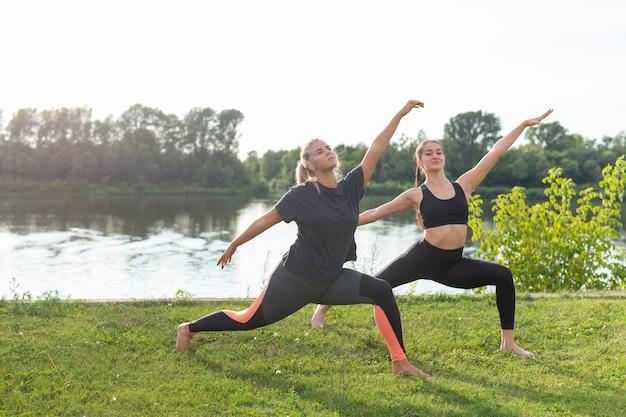 Estilo de vida saudável e conceito de harmonia - jovens garotas fazendo ioga ao ar livre