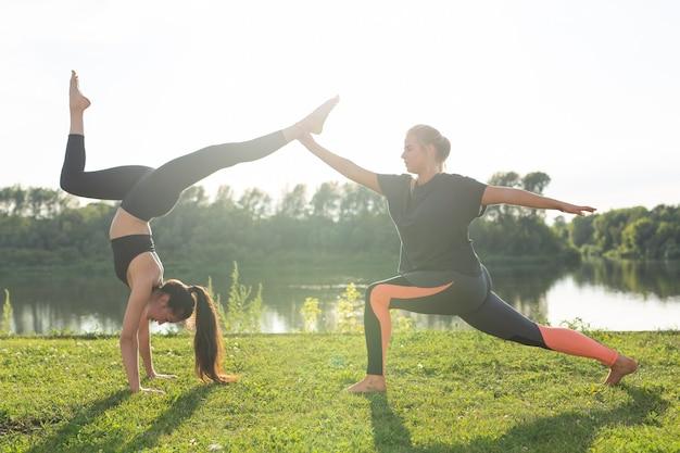 Estilo de vida saudável e conceito de pessoas - mulheres flexíveis fazendo ioga no parque de verão