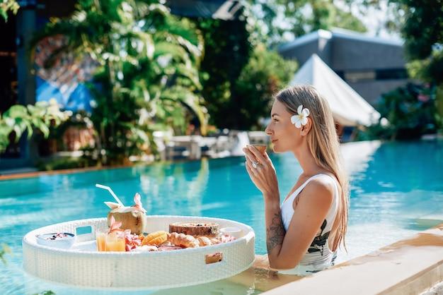 Estilo de vida saudável e férias na tailândia. retrato de uma jovem mulher branca que bebe suco nadando em uma piscina com mesa flutuante.