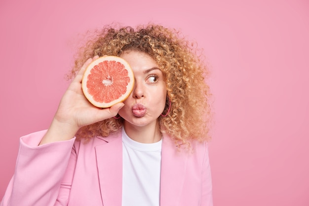 Estilo de vida saudável e vitaminas. mulher adorável com cabelo crespo e encaracolado mantém os lábios dobrados, cobre os olhos com metade da toranja mantém a dieta vestida com roupas formais, isolada sobre o espaço em branco da parede rosa
