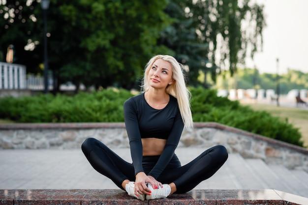 Estilo de vida saudável esportes. jovem mulher bonita com roupas esportivas sentar no parque da cidade