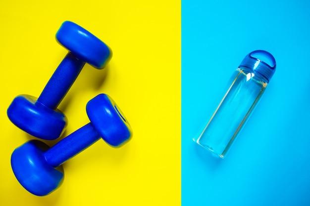 Estilo de vida saudável, hábitos saudáveis. água de desintoxicação, salada de frutas, halteres de equipamentos de esporte no espaço de cópia de vista superior de fundo azul