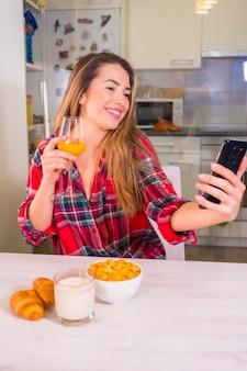 Estilo de vida saudável, loira caucasiana com suco de laranja no café da manhã e gravação de vídeo para redes sociais