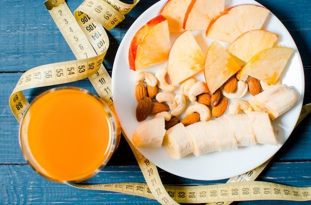 Estilo de vida saudável. maçã e suco de laranja em uma mesa de madeira
