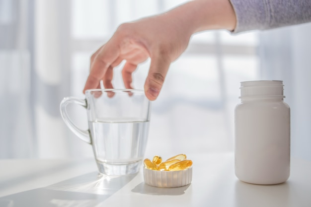 Estilo de vida saudável, medicamentos, suplementos nutricionais e conceito de pessoas - close up de mãos do sexo masculino segurando pílulas com cápsulas de óleo de fígado de bacalhau e copo de água