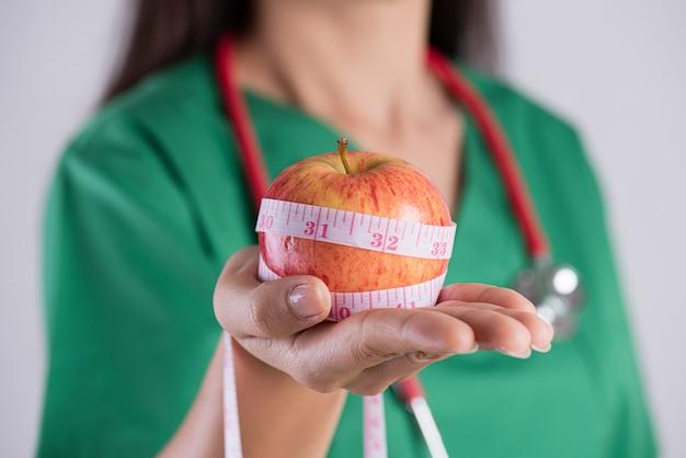 Estilo de vida saudável, médico segurando a fita métrica em torno da maçã verde fresca.