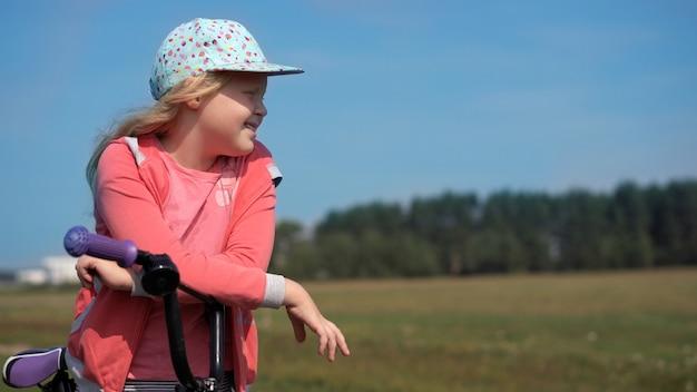 Estilo de vida saudável - menina com uma bicicleta andando em um campo perto da cidade