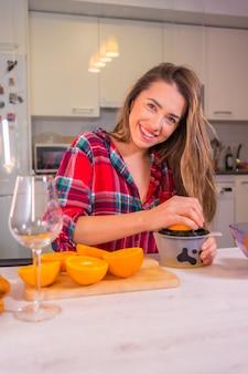 Estilo de vida saudável, mulher loira caucasiana se divertindo no café da manhã com suco de laranja fresco na cozinha
