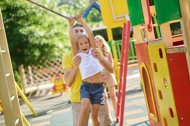 Estilo de vida saudável. pai adulto jovem e carinhoso e sua filha jogando esportes no parquinho e observando a mãe atrás