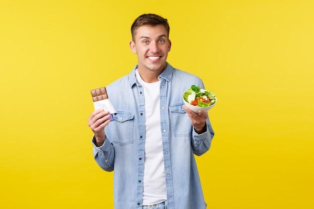 Estilo de vida saudável, pessoas e conceito de comida. cara alegre sorridente, mostrando a barra de chocolate e a salada, parecendo feliz e otimista, dizendo que se encaixa com a dieta, fundo amarelo de pé.