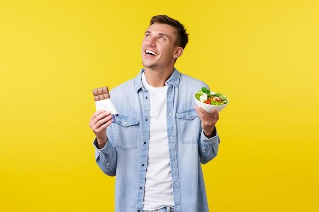 Estilo de vida saudável, pessoas e conceito de comida. cara feliz sonhadora sorridente, olhando o canto superior esquerdo, segurando a tigela com salada e barra de chocolate, fundo amarelo de pé. copie o espaço