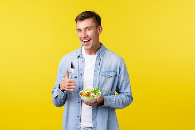 Estilo de vida saudável, pessoas e conceito de comida. homem feliz e sorridente mostrando o polegar para cima satisfeito com um delicioso café da manhã, comendo salada, fazendo dieta, tentando ficar em forma, fundo amarelo de pé.
