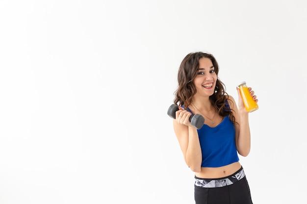 Estilo de vida saudável, pessoas e conceito de esporte - mulher com suco saudável bebendo para esporte e fitness em fundo branco com espaço de cópia