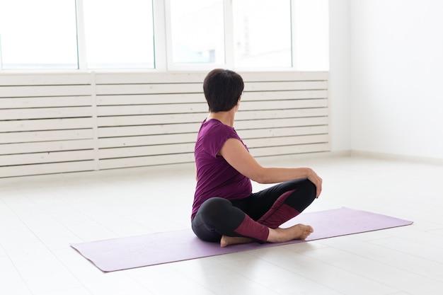 Estilo de vida saudável, pessoas e conceito de esporte. mulher de meia-idade fazendo ioga