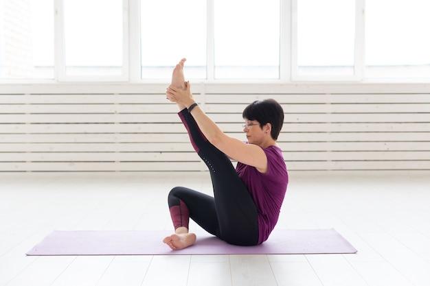 Estilo de vida saudável, pessoas e conceito de esporte - mulher de meia idade fazendo ioga.